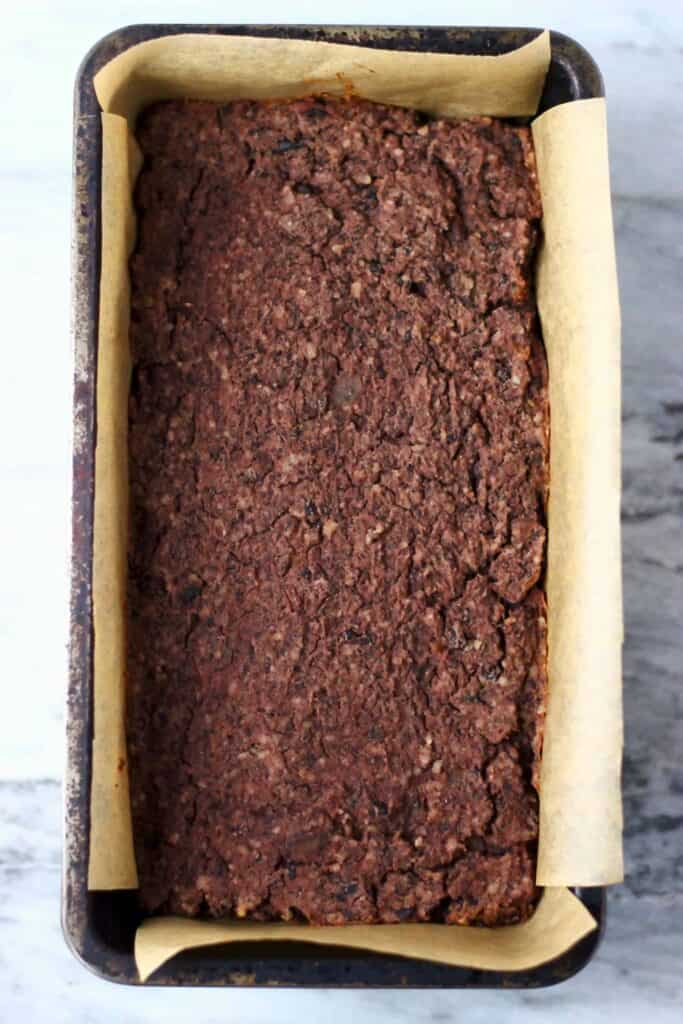 Cooked meatloaf in a loaf tin lined with brown baking paper against a marble background