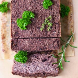 A black meatloaf with two slices taken from it on a sheet of brown baking paper scattered with fresh green herbs