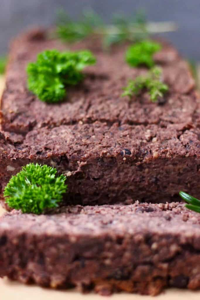 A black meatloaf with two slices taken from it scattered with fresh green herbs