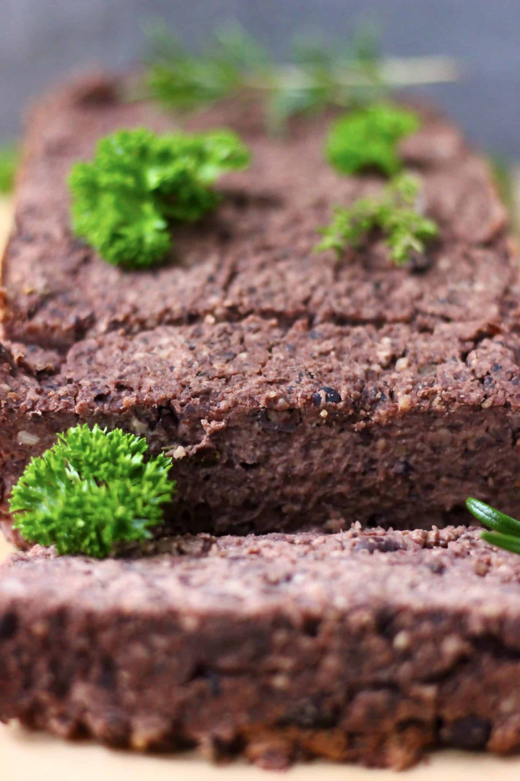 A black bean vegan meatloaf with two slices cut from it