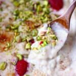 Rice pudding in a grey rectangular baking dish topped with chopped pistachios and fresh raspberries with a wooden spoon lifting up a mouthful of it