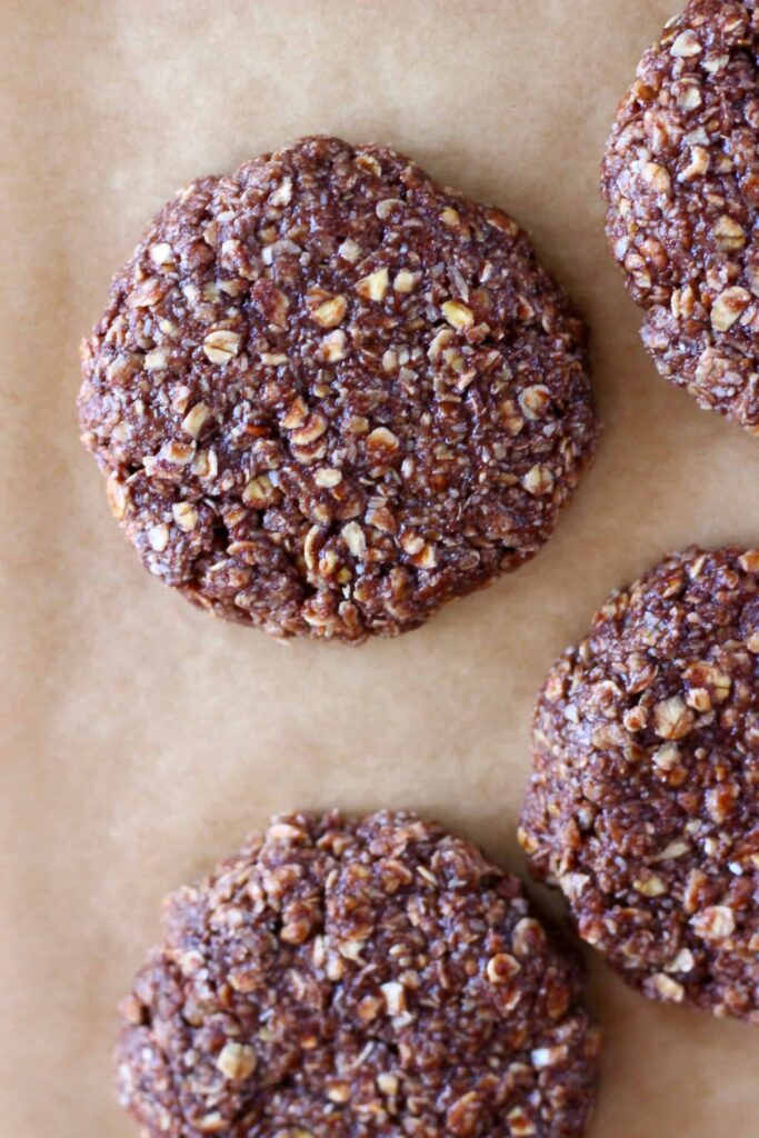 Four raw chocolate oatmeal cookies on a sheet of brown baking paper