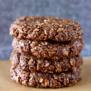 Four gluten-free vegan chocolate no-bake cookies stacked on top of each other on a sheet of baking paper