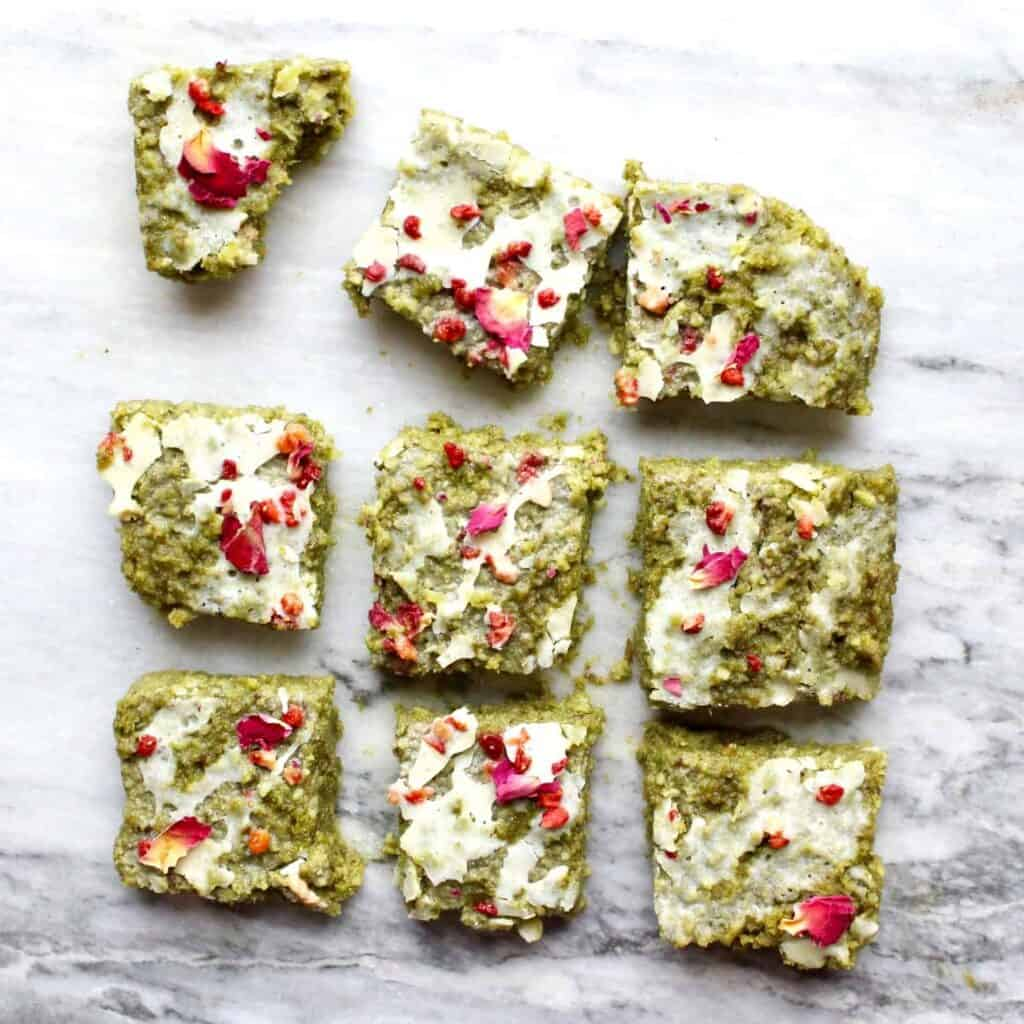 Photo of nine green brownies drizzled with white chocolate and decorated with rose petals on a marble background