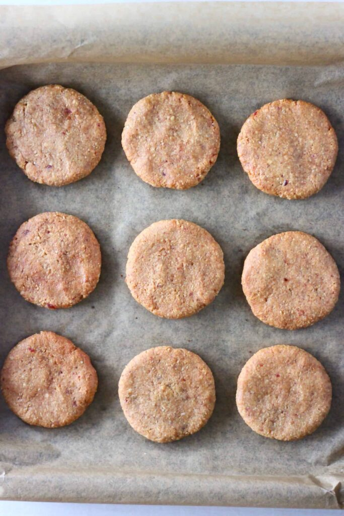 Nine golden brown almond butter cookies on a sheet of brown baking paper
