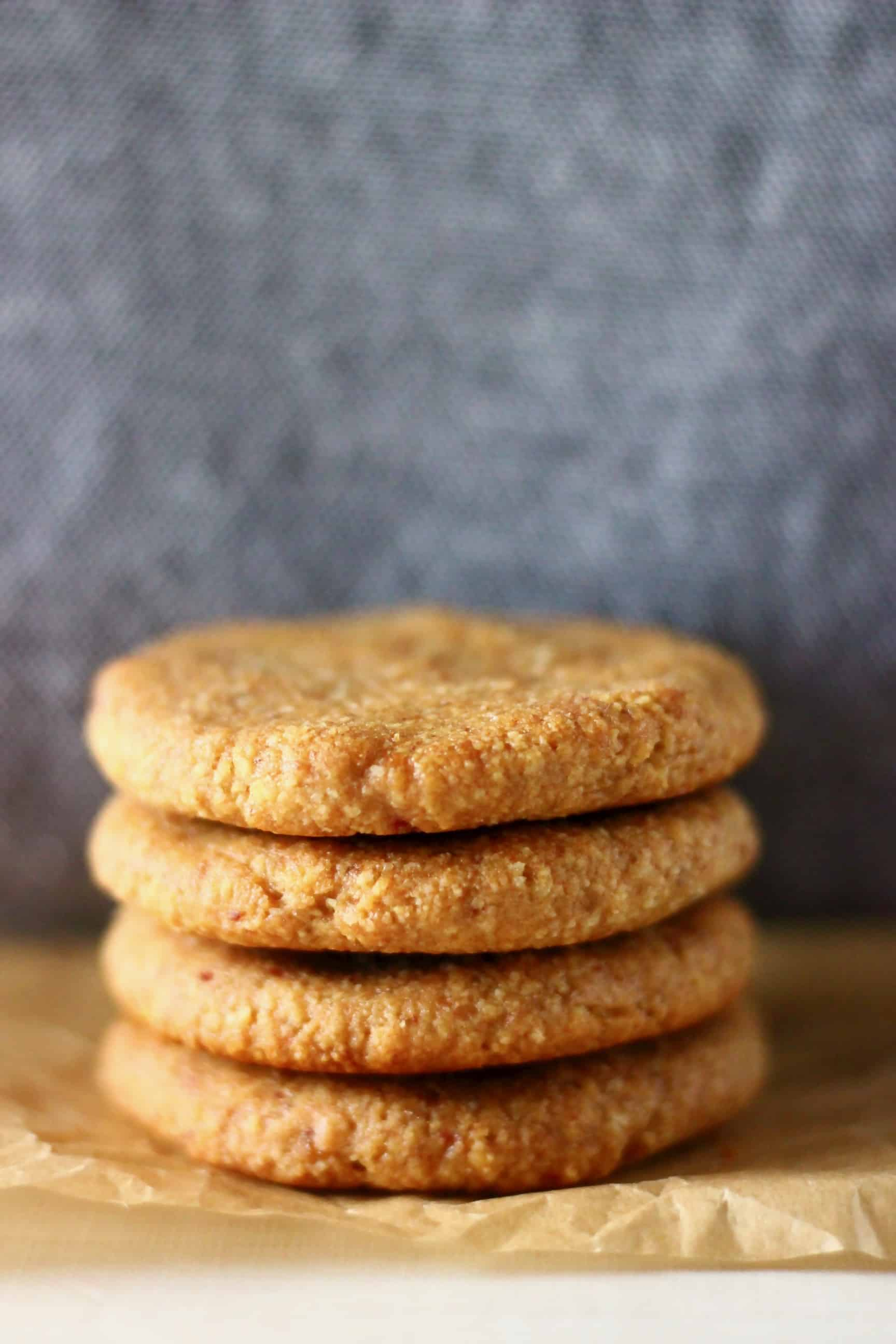 Four almond butter cookies stacked on top of each other on a sheet of  baking paper