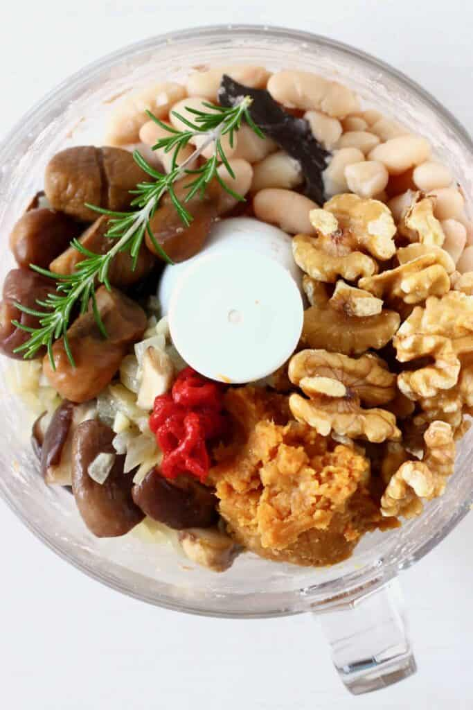 White beans, fried mushrooms, miso, tomato paste, walnuts, chestnuts and a sprig of rosemary in a food processor against a white background