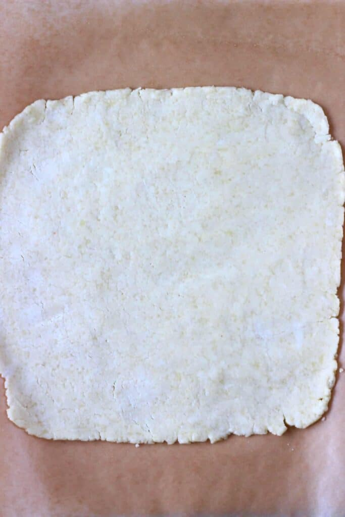A square of raw pastry dough on a sheet of brown baking paper