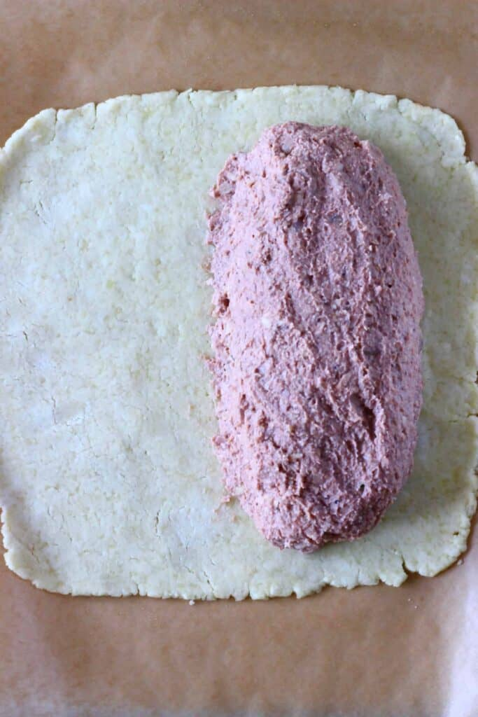 A square of raw pastry dough with a sausage shaped raw vegan wellington filling on top of it on a sheet of brown baking paper