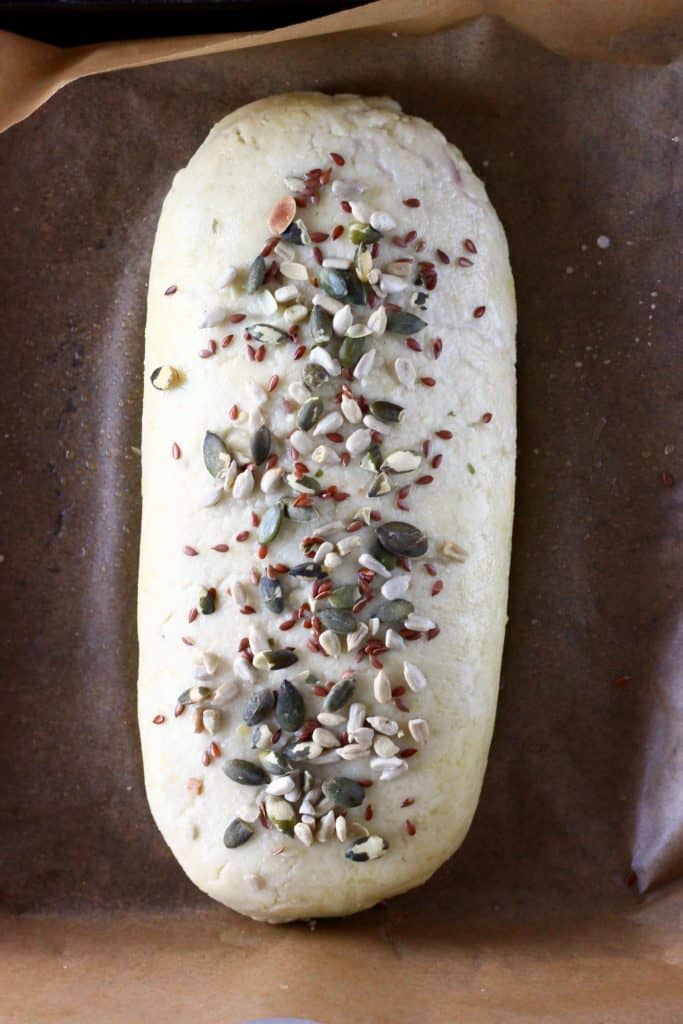 A raw wellington sprinkled with mixed seeds on a sheet of brown baking paper