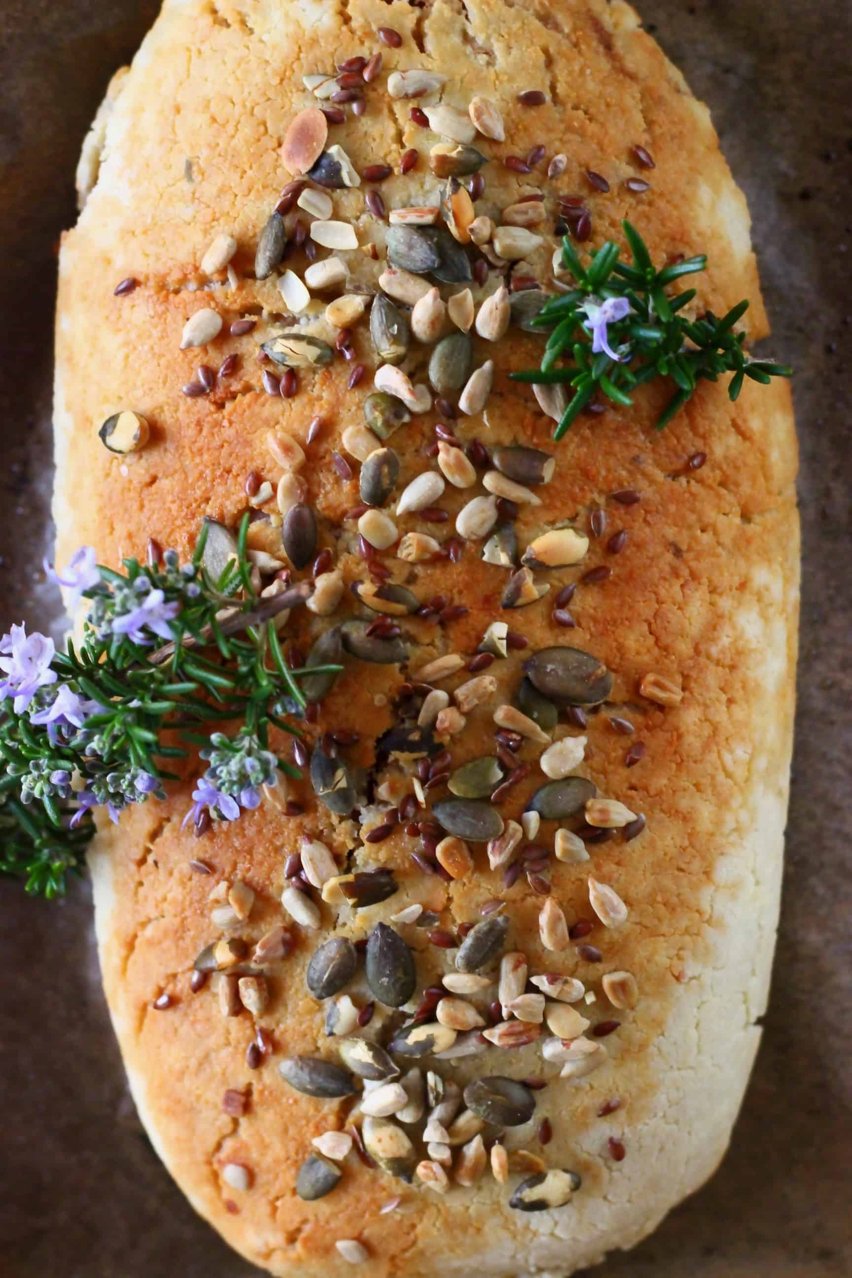 A golden brown vegan wellington topped with mixed seeds and sprigs of rosemary on a baking tray