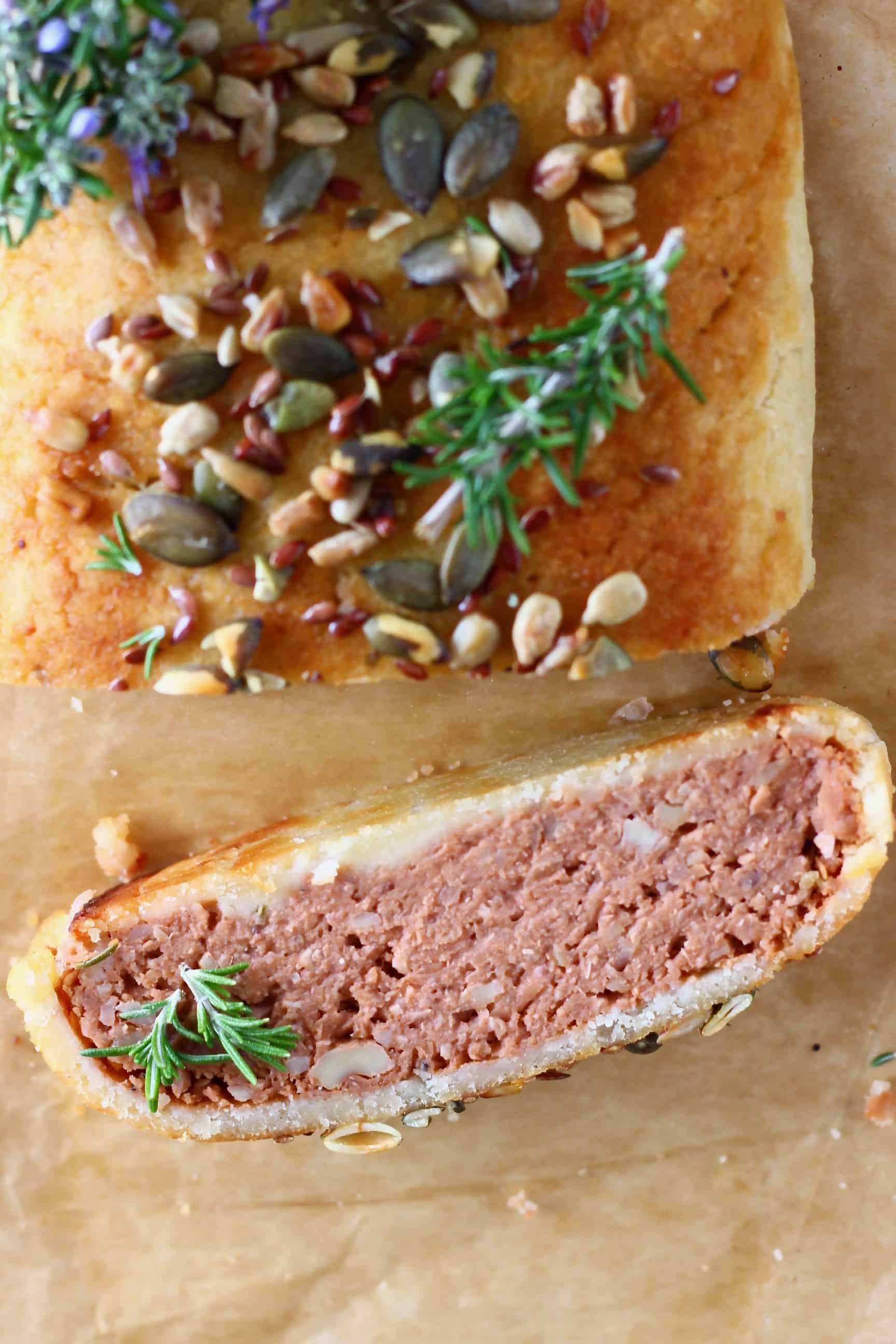 A vegan Wellington topped with mixed seeds with a slice on the side on a sheet of baking paper