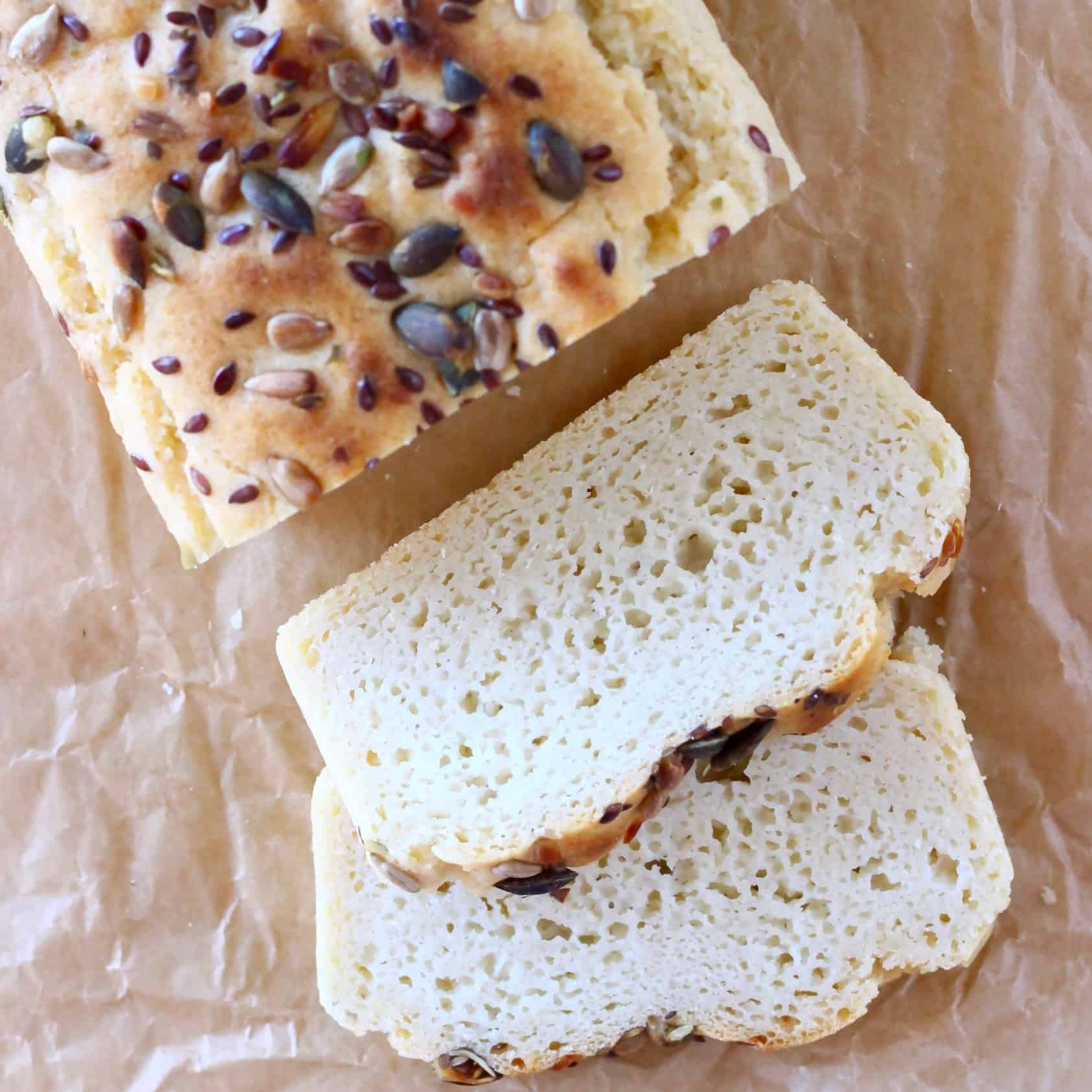 A loaf of brown bread sprinkled with mixed seeds with two slices of white bread next to it against a sheet of brown baking paper