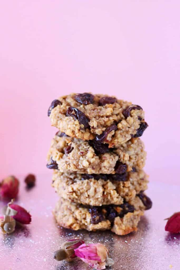 Four oatmeal cookies with raisins stacked up on a silver surface against a light pink background