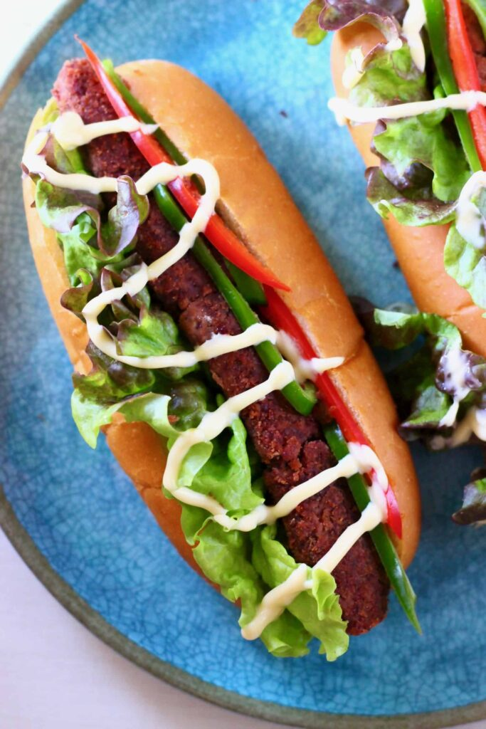 Photo of a hot dog with peppers and lettuce drizzled with mayonnaise on a blue plate