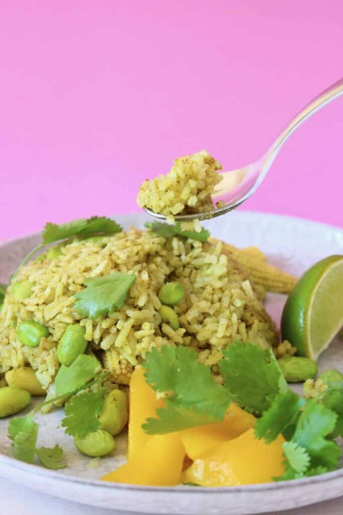 A mound of green rice on a plate with a spoon lifting up a mouthful of it against a pink background
