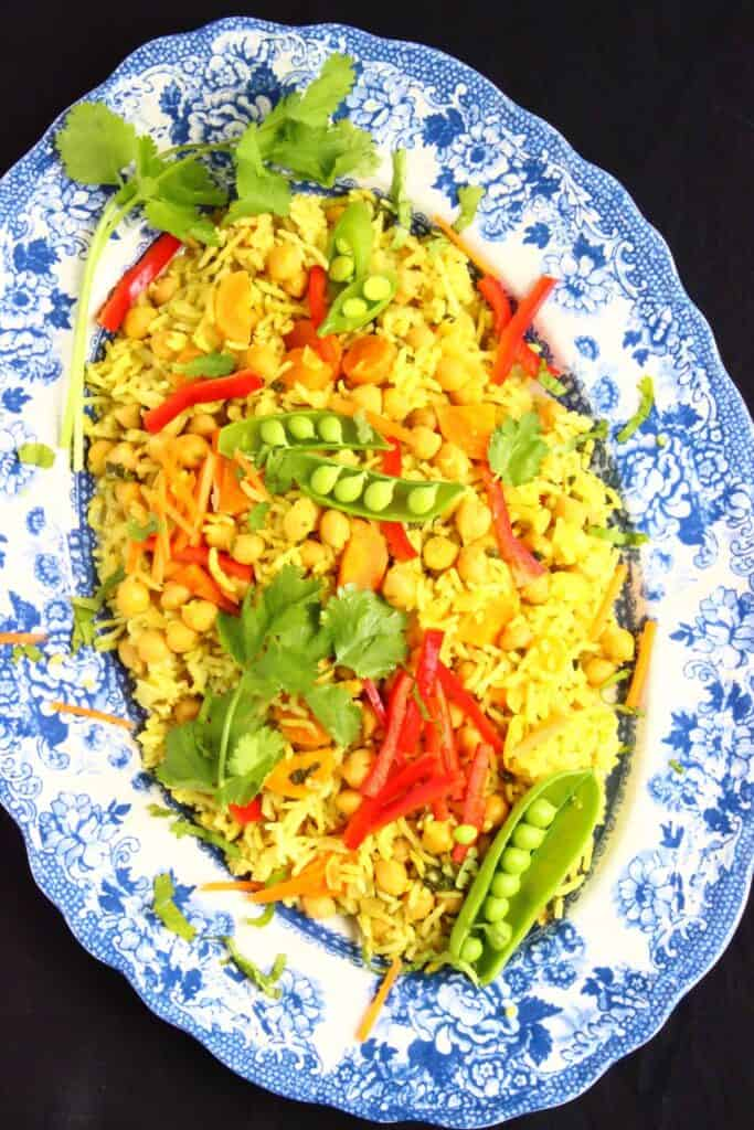 Photo of yellow rice with green and red vegetables on a blue patterned plate against a black background