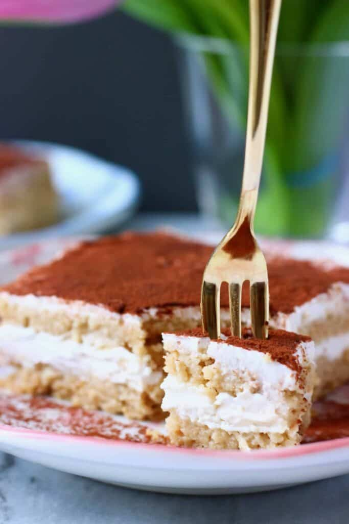 Photo of a slice of tiramisu with a bite taken out of it on a white plate with pink flowers and a gold fork taking a mouthful