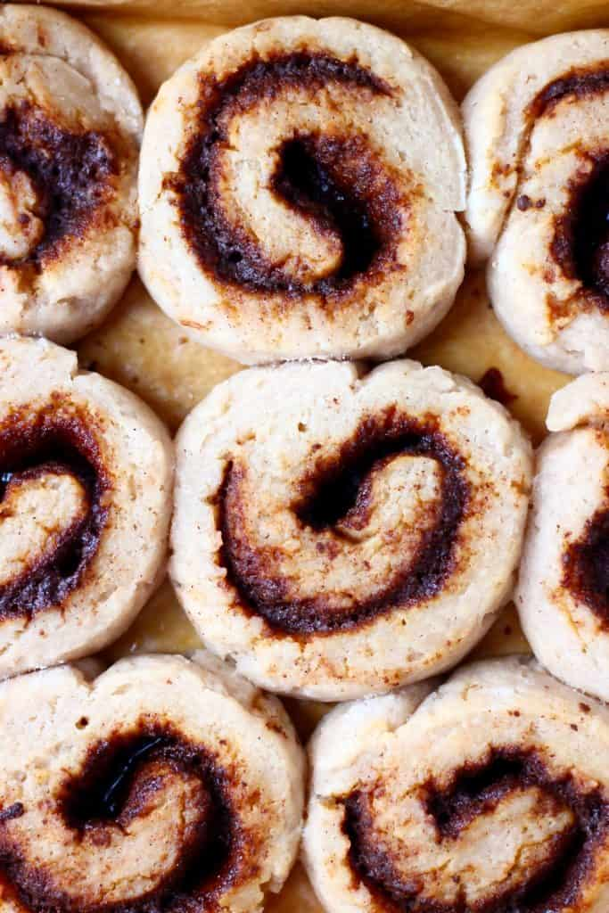 Photo of nine cinnamon rolls against a sheet of brown baking paper