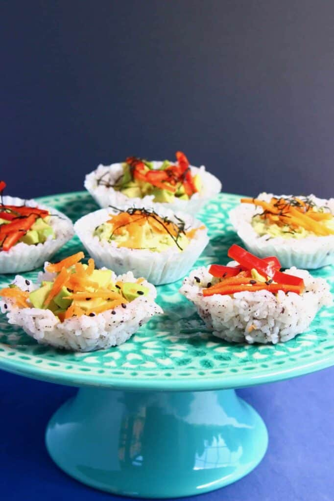 Six muffin-shaped sushi topped with grated carrot and shredded red pepper on a green cake stand against a grey background