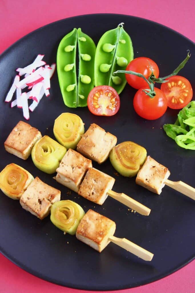 Tofu cubes and sliced leeks on three wooden skewers on a black plate