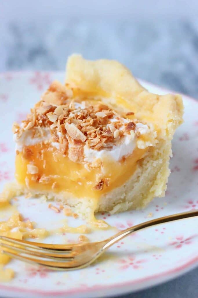 A slice of pie filled with lemon curd topped with cream and toasted coconut on a white plate with pink flowers with a small gold fork