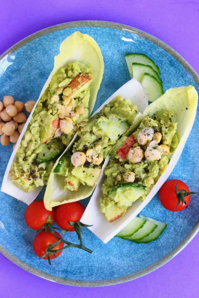 Three chicory boats filled with avocado, chickpeas, apples and cucumber on a blue plate against a purple background