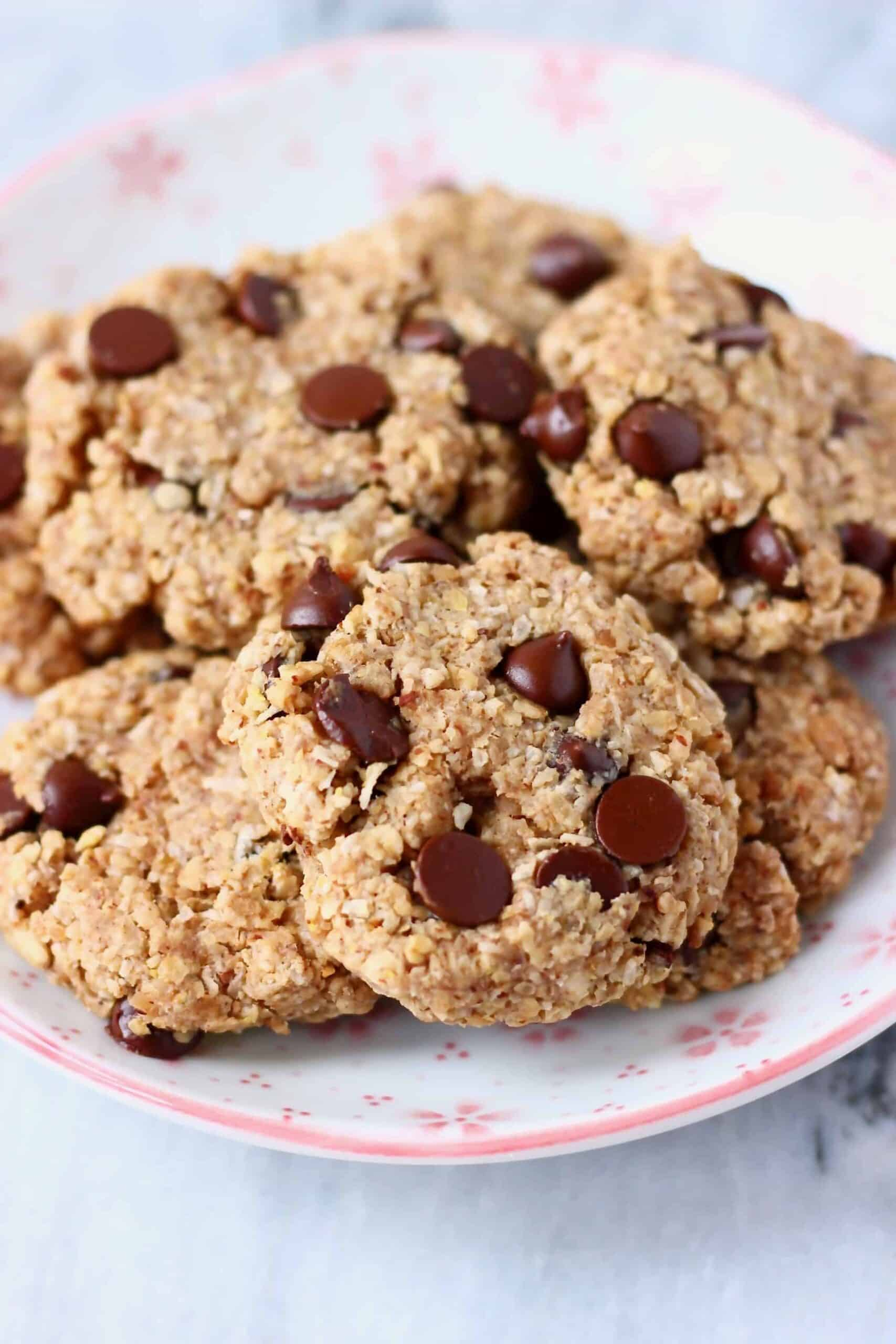 Photo of a pile of chocolate chip cookies on a white plate decorated with pink flowers