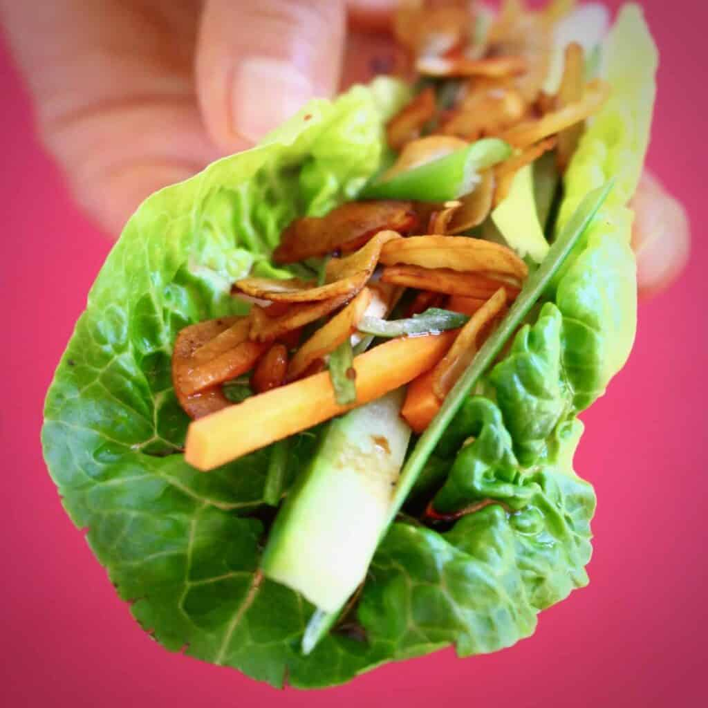 A lettuce wrap filled with brown coconut pieces, sliced spring onions and cucumber held up with a hand against a bright pink background