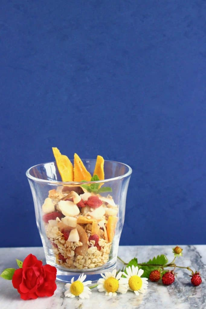 Granola in a glass cup topped with dried mango and a sprig of mint on a marble surface against a dark blue background