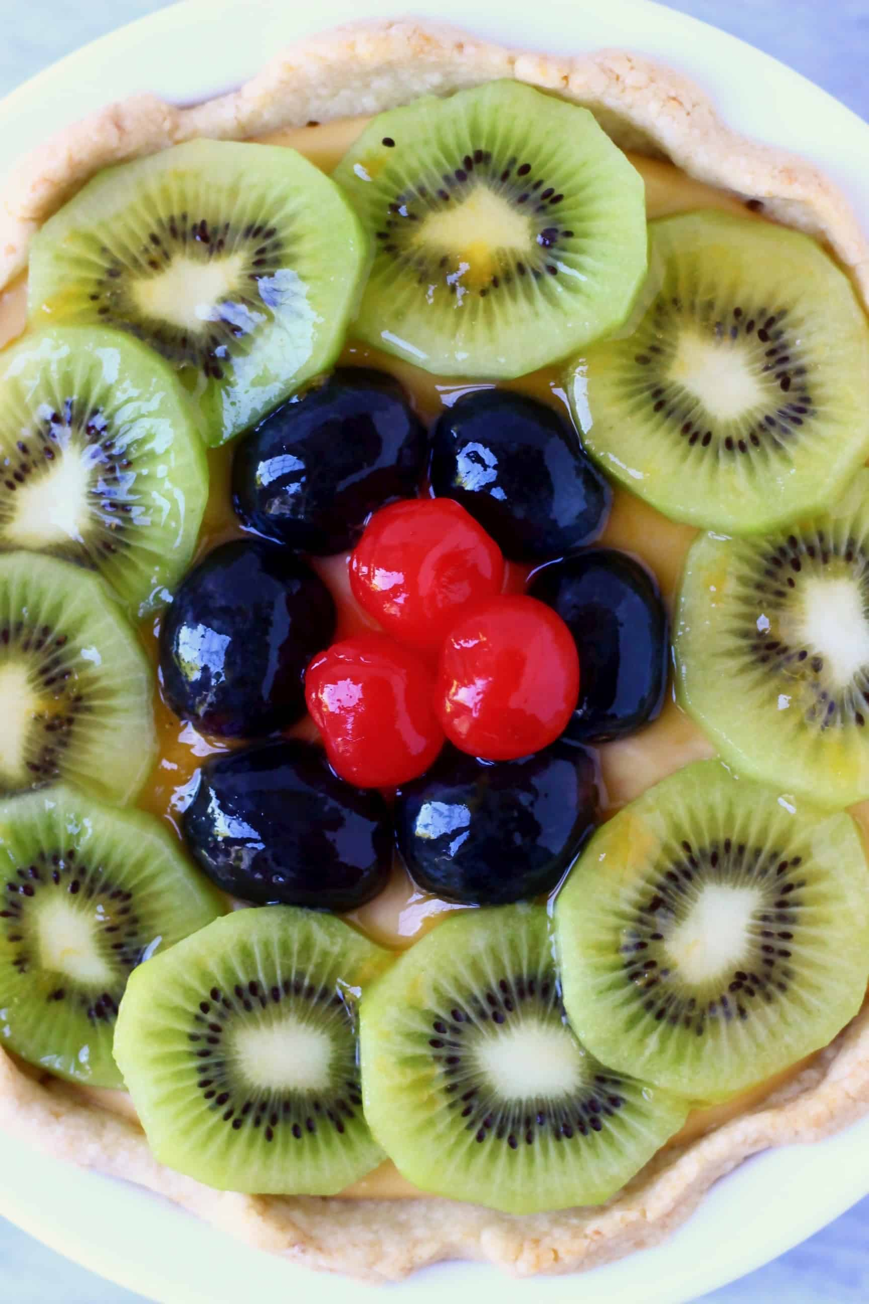 Kiwi slices, black grapes and red cherries on top of a fruit tart in a white pie dish