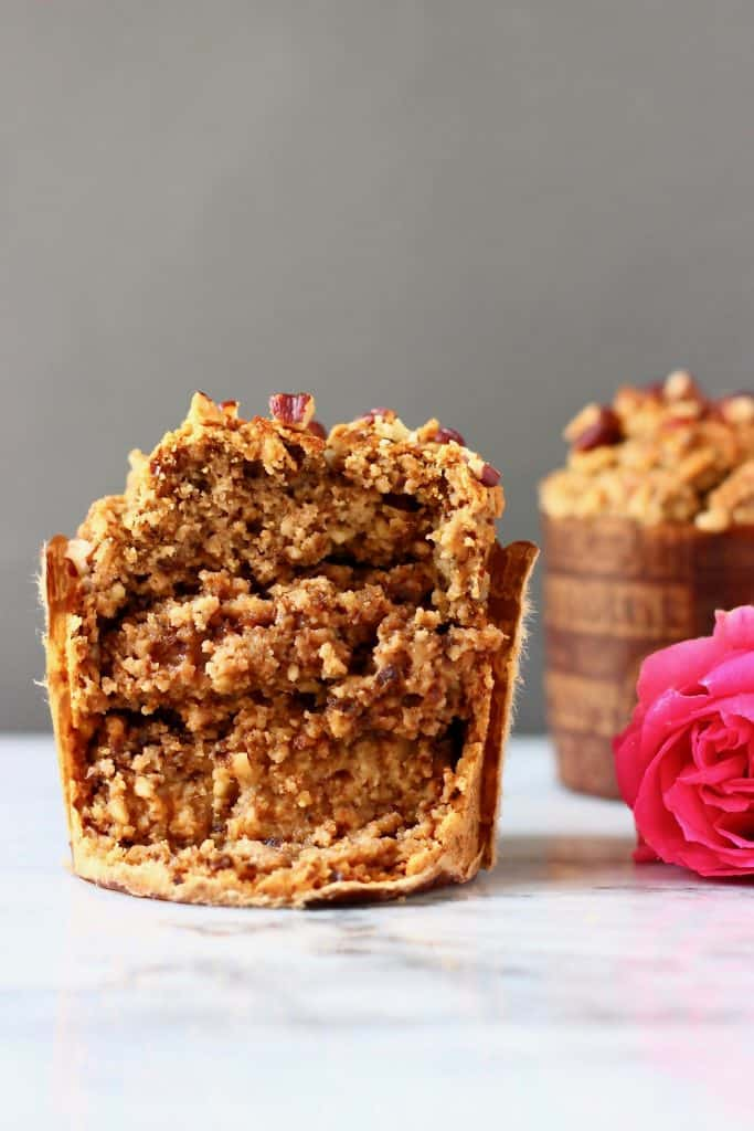 Photo of two brown muffins with a pink rose with one of the muffins cut in half