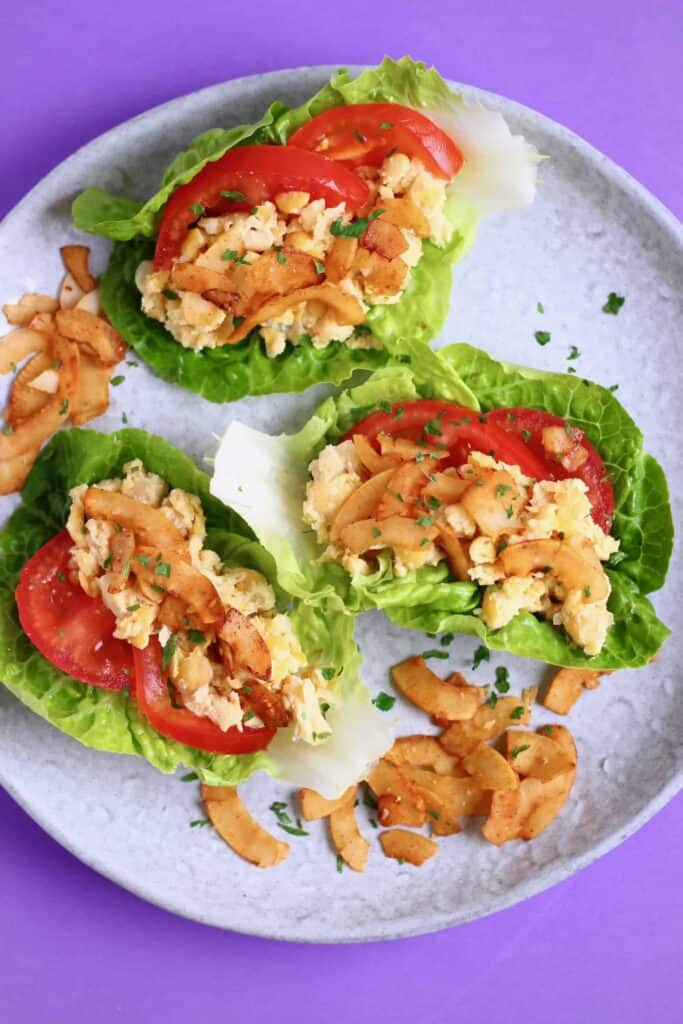 Three lettuce cups filled with creamy chickpeas, coconut bacon and tomatoes on a grey plate against a purple background
