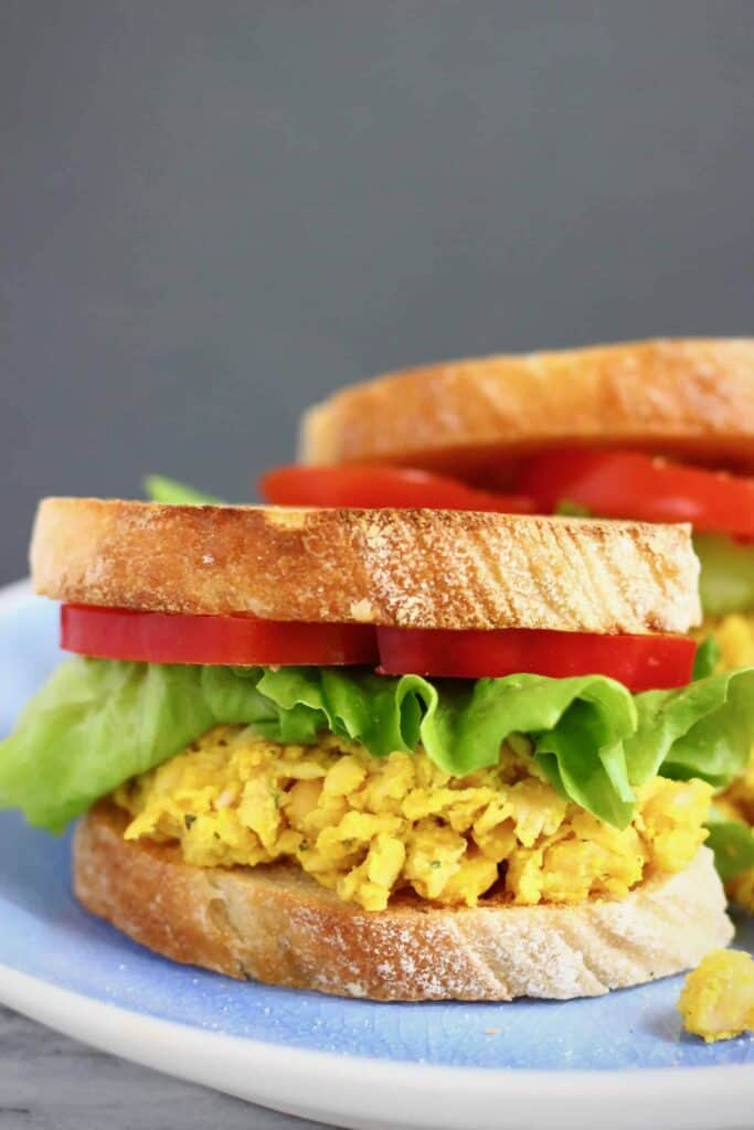 Two sandwiches with curried chickpeas, lettuce and sliced red pepper against a grey background