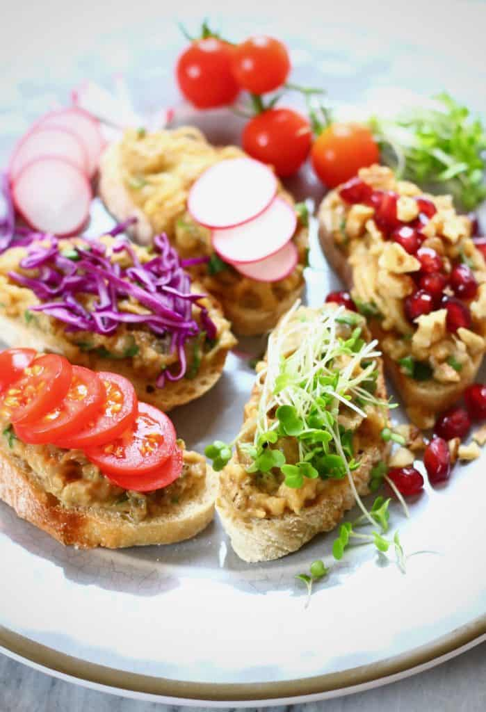 Five slices of bread topped with smashed eggplant, cress, sliced tomato, shredded red cabbage, sliced radish and pomegranate arils on a grey plate