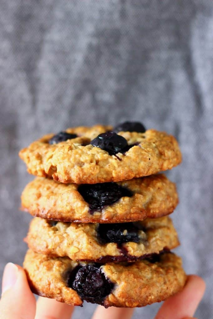 Four blueberry cookies stacked up on top of each other and held up with a hand against a grey background
