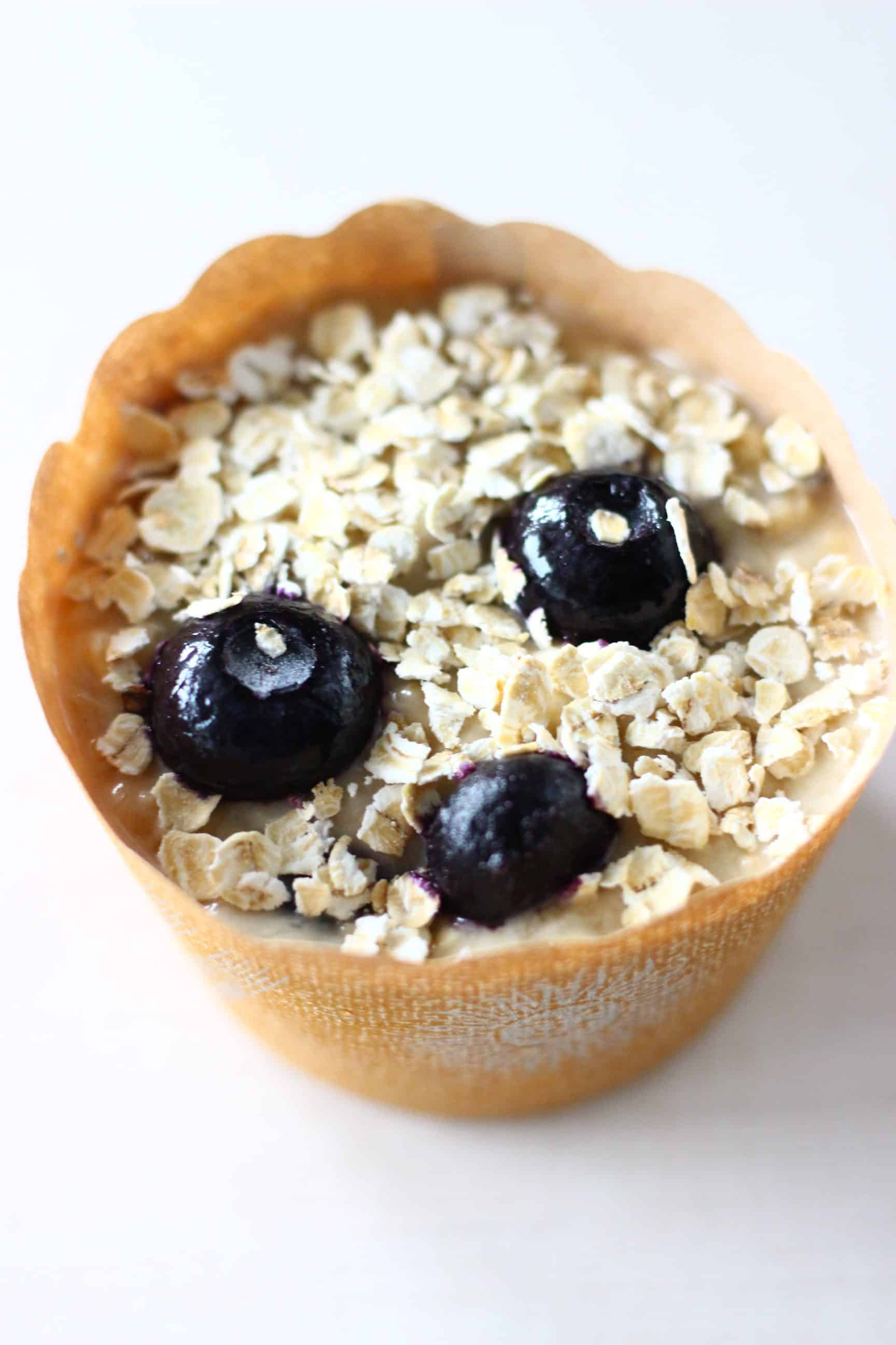 A brown muffin case filled with raw gluten-free vegan blueberry oatmeal muffin batter sprinkled with oats
