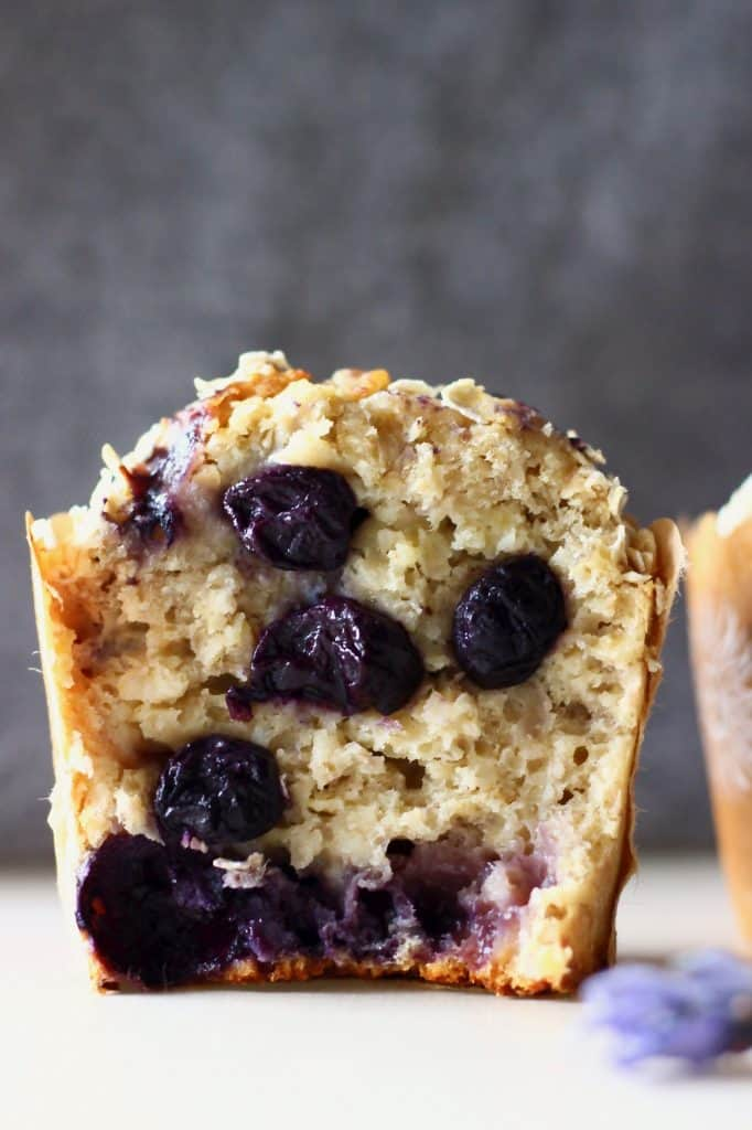 A halved blueberry muffin on a white surface against a grey background