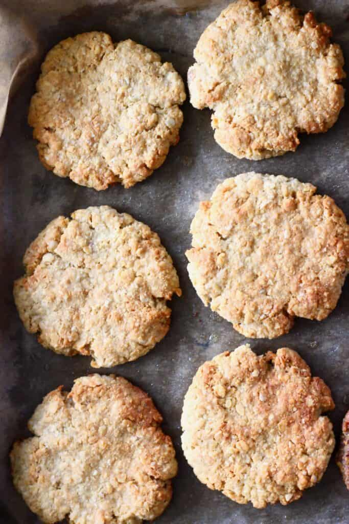 Six golden brown cookies on a baking tray covered in brown baking paper