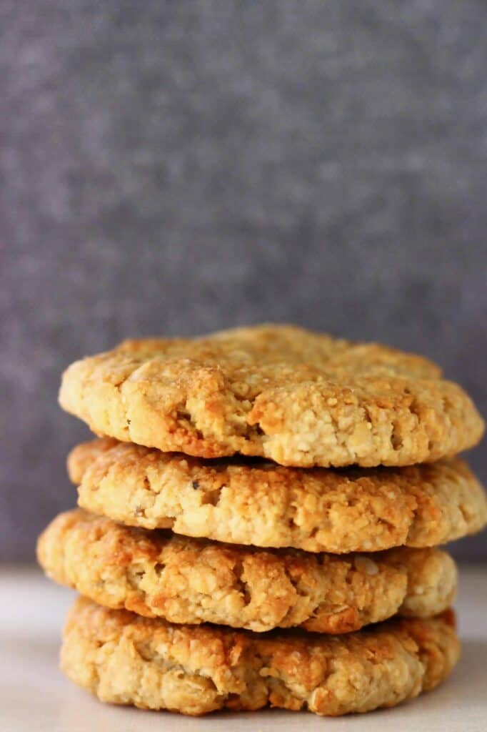 Four golden brown cookies stacked up on top of each other against a grey background