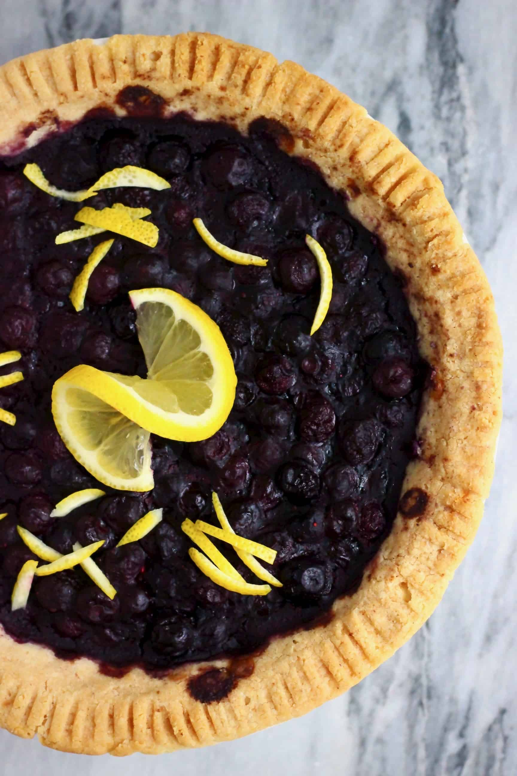 A vegan blueberry pie decorated with lemon peel and a slice of lemon against a marble background