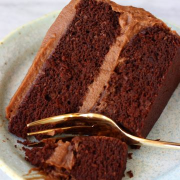 A slice of gluten-free vegan chocolate cake with chocolate frosting on a blue plate with a gold fork