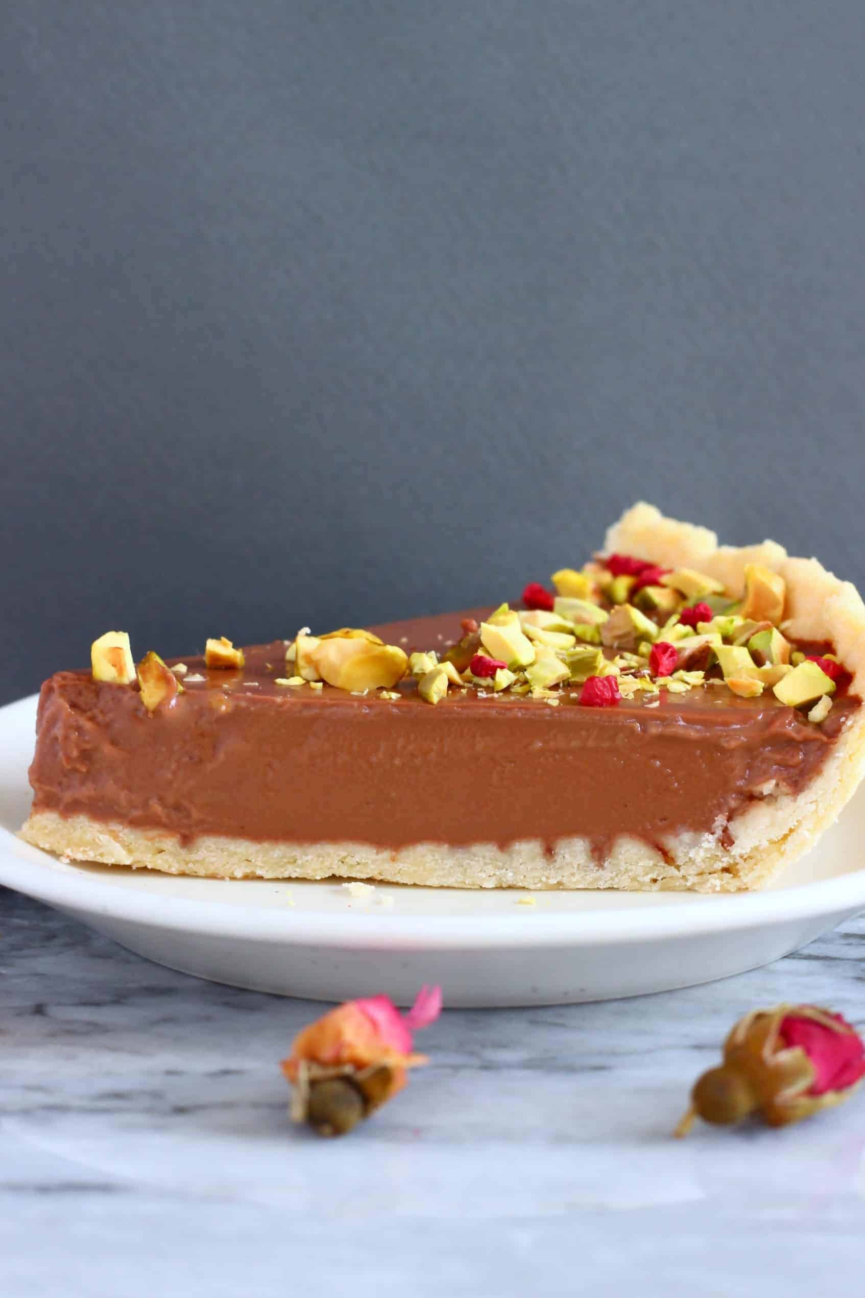 A slice of chocolate tart topped with chopped pistachios and freeze-dried raspberries on a white plate against a grey background