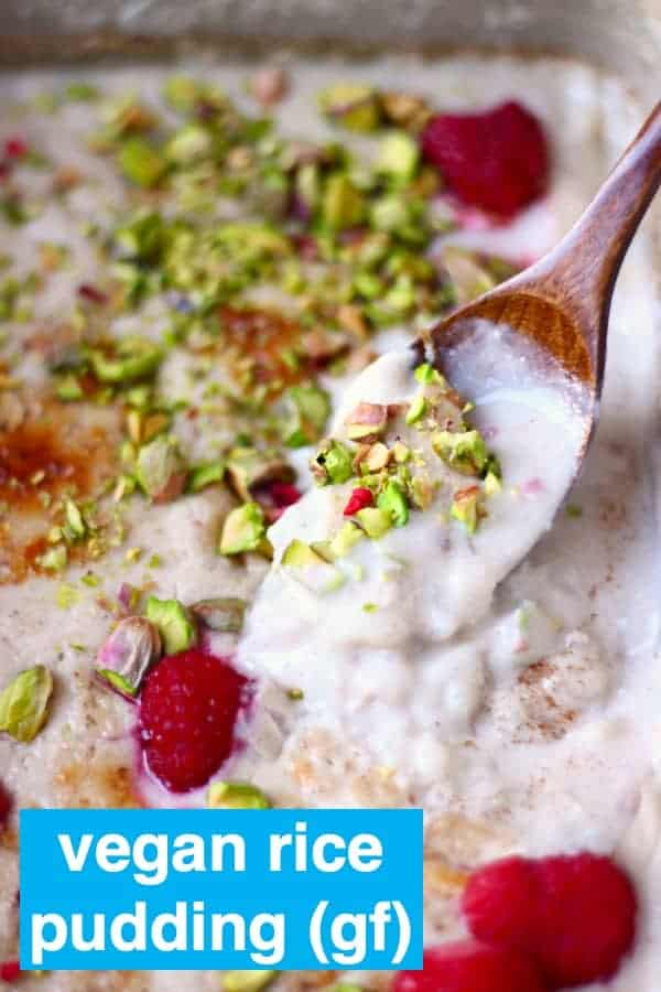 Rice pudding in a grey rectangular baking dish topped with chopped pistachios and fresh raspberries