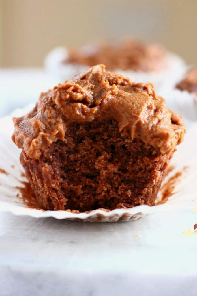 A chocolate cupcake topped with chocolate frosting in a white cupcake wrapper and another cupcake in the background