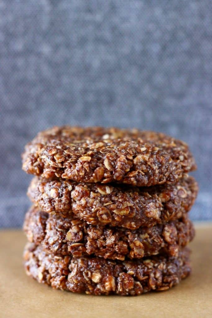 Four raw chocolate oatmeal cookies stacked on top of each other on a sheet of brown baking paper against a grey background