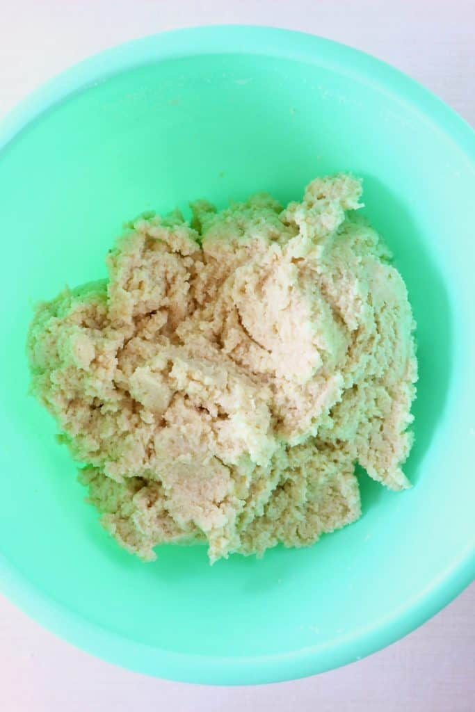 Raw bread dough in a green bowl against a white background