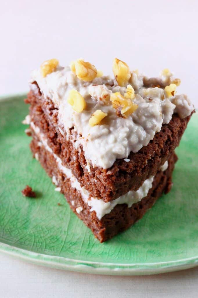 A slice of chocolate cake topped with white frosting and walnuts on a green plate against a white background