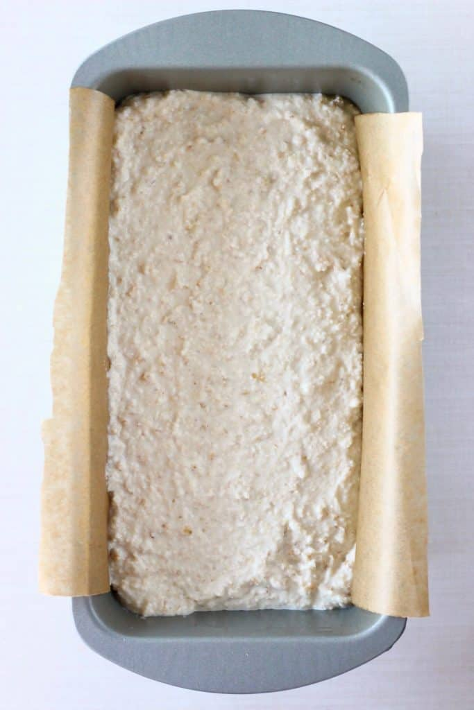 Photo of white bread batter in a silver loaf tin lined with brown baking paper against a white background