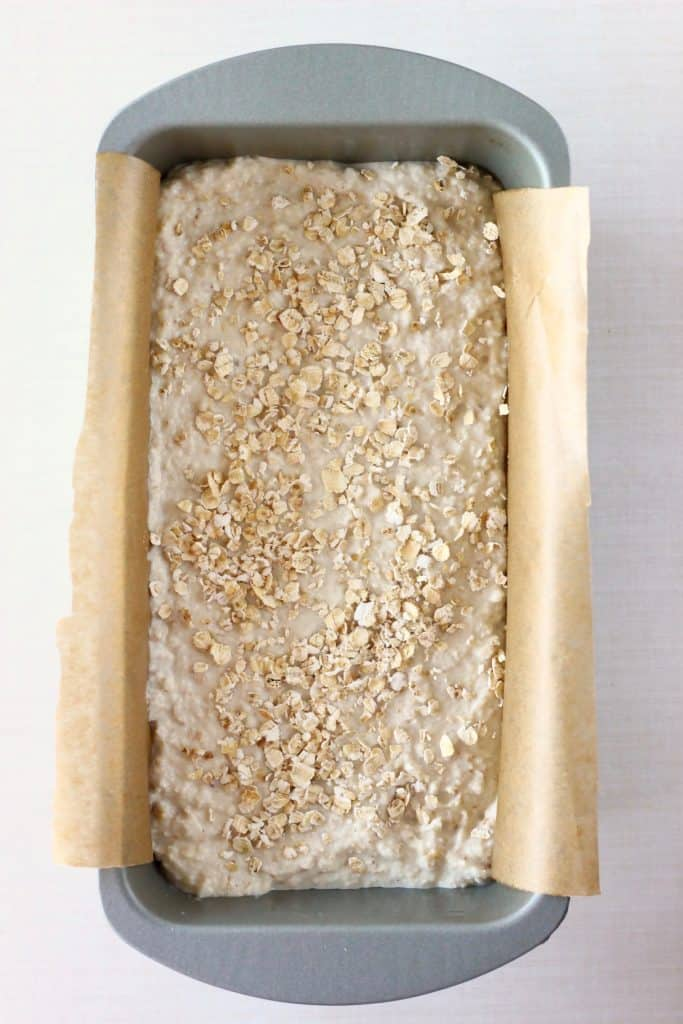 Photo of white bread batter sprinkled with oats in a silver loaf tin lined with brown baking paper against a white background